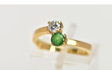 A YELLOW METAL CROSSOVER RING, set with a round brilliant cu...