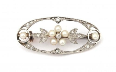 A gold Belle Epoque diamond and pearl brooch. In the center a cluster of seed pearls as flower surrounded by a border of foliage set with single cut diamonds. The gold was found below the Dutch legal gold grade of 14 karat. Gross weight: 3.3 g.