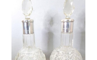 A pair of cut-glass silver-mounted scent bottles; each with ...