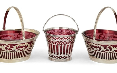 Three Victorian silver sweetmeat baskets with red glass liners, comprising: a pair of oval baskets, London, c.1887, Daniel & John Wellby, both very faintly gilded, 11.2 cm long, 5.1cm high, and an earlier round example, London, c.1882, Rosenthal...