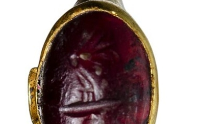 A late hellenistic gold ring with garnet intaglio. Butterfly with...