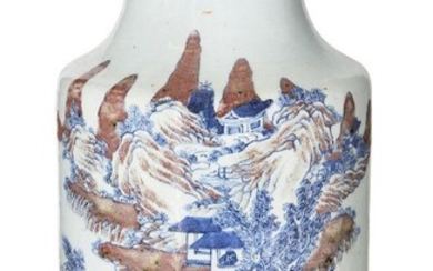 A Chinese porcelain underglaze copper-red and blue cylindrical vase, 18th century, painted with an expansive mountainous landscape with a scholar and attendant crossing a bridge on horseback, a pair of scholars sat in discussion on a rocky outcrop...