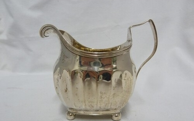 A George III silver cream jug of rounded oblong bellied form...