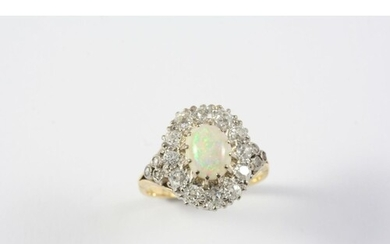 AN OPAL AND DIAMOND CLUSTER RING the oval-shaped solid white...