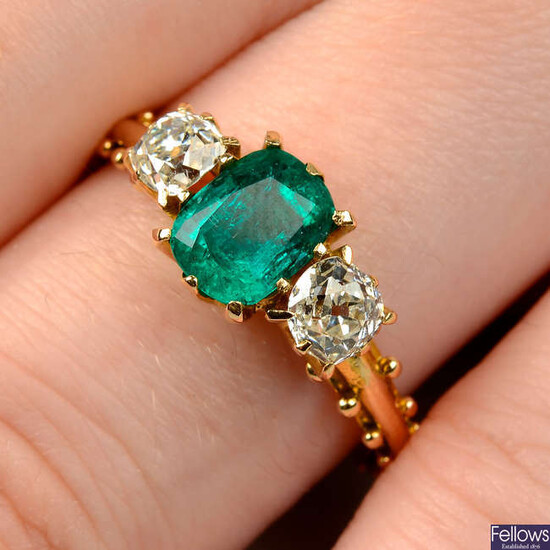An emerald and old-cut diamond three-stone ring.