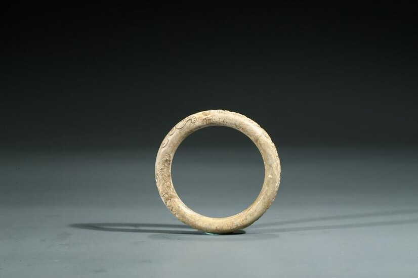 A CALCIFIED JADE 'CHILONG AND INSCRIPTION' BANGLE
