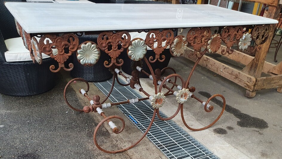 A WROUGHT IRON BASED MARBLE TOP ALFRESCO TABLE