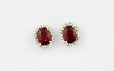 A pair of 18ct white gold (stamped 750) cluster earrings set with an oval cut ruby surrounded by brilliant cut diamonds, approx. 4.96ct rubi