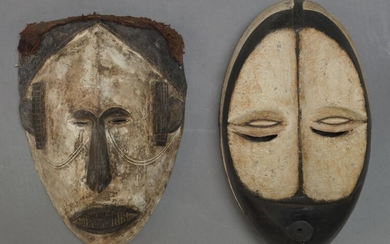 An Igbo mask, Nigeria, second half 20th Century, with applied white pigment and carved stylised features, 31cm high together with another African mask, 31cm high (2)