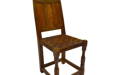 An oak side chair with triple fielded panel back over a wove...