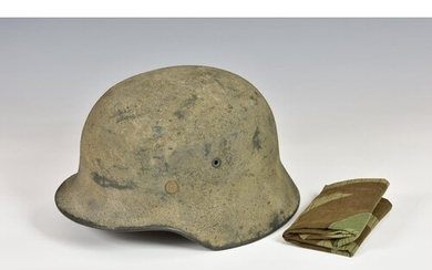 A WWII German M40 camouflaged steel helmet and liner with he...