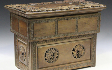 A late 19th/early 20th century Indian carved hardwood dressing box, finely worked with bands of foli