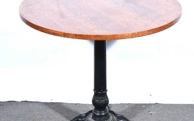 A reproduction cast iron pub table, and an oak stool.