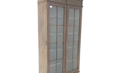 Early 20th century oak bookcase on cupboard, frieze with...