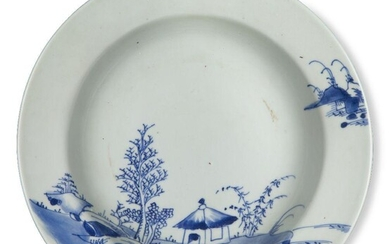 A Chinese porcelain blue and white 'Empty Sky' bowl excavated from the Nanking Cargo, circa 1750, painted with a house in a coastal landscape scene, 23.2cm diameter Provenance: with Christie's Nanking Cargo paper label to base that reads 'Lot 4134'