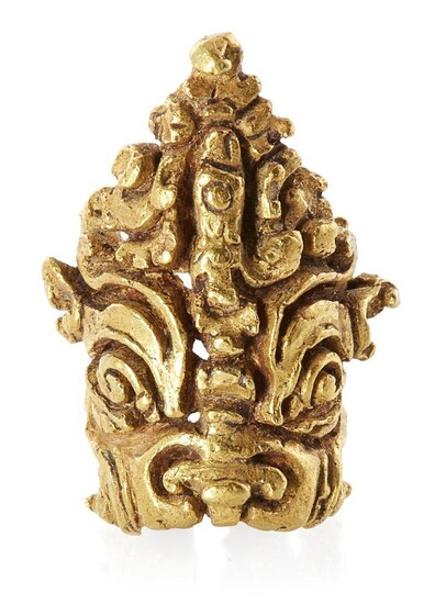 A Gupta gold hair ornament of Kirtimukha, India, 5th-8th century, in the form of a male mask with deep set eyes and exaggerated brows wearing a pointed crown heavily cast and carved in deep relief, weight 9.4 grams The exact function of these...