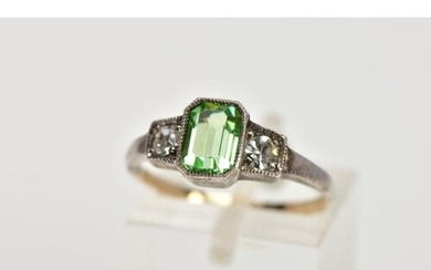 A YELLOW AND WHITE METAL DRESS RING, centring on an emerald ...