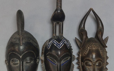 A Yaore mask, second half 20th Century, with carved bird headrest, the oval face with painted decoration and stylised features, 44cm high, together with two other Yaore masks each 36cm high (3)