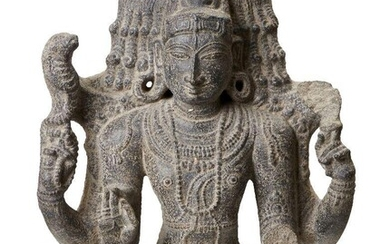 A black stone sculpture of Shiva, India, 19th century in a 10th century style, carved wearing a bejewelled tiered tiara, the elegant rounded face with almond eyes, straight nose and bow lips, and flanked with pendulous earlobes, wearing strands of...