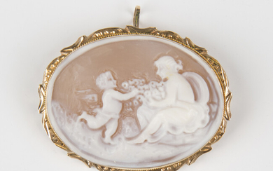 A gold mounted oval shell cameo pendant brooch, carved as a maiden with Cupid, the shaped surround w