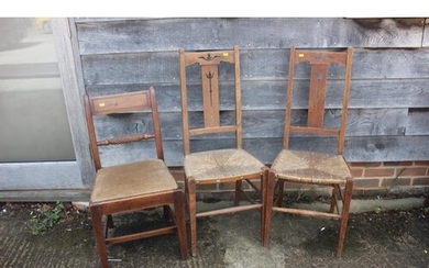 A pair of Arts & Crafts rush seat elbow chairs with triple s...