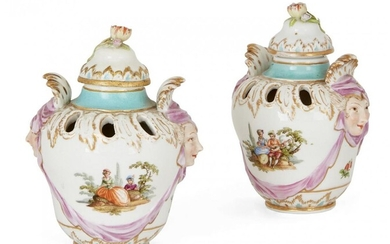 A pair of Berlin porcelain two-handled pot pourri vases and covers, late 19th century, each painted with a vignette of figures in a landscape, the mask head handles with puce drapery, blue sceptre mark, 14cm high (2)