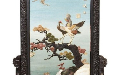 A Chinese lacquered and inlaid hardwood table screen, 20th century, applied to one side with a pair of cranes on pine, inlaid with soapstone, coloured hardstone, bone and hardwood, bearing an apocryphal Qianlong mark next to inscription, the...
