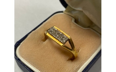 A diamond three stone ring, with bifurcated shoulders and se...