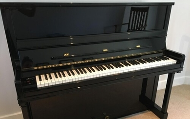 Feurich (c1980) An upright piano in a traditional bright ebo...