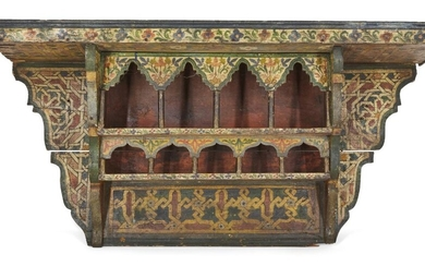 A polychrome painted wood shelving unit, Morocco or Spain, late 19th-early 20th century, decorated i n red, green and yellow with geometric designs and flowers, 80.5cm. high x 40cm. diam.