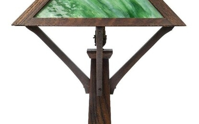 An Arts & Crafts 'Mission Style' oak and marbled glass table lamp, probably American, c.1920, Stained oak frame supporting four marbled green and white glass panels, united to the central column by angled supports, on a stepped, square foot, 57 cm...