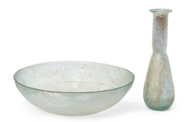 A Roman pale blue shallow hemispherical glass dish with a band of medial wheel-cut grooves on the interior, circa 1st Century B.C.-1st Century A.D., 13.4cm diam, 3.4cm high and a pale blue glass flask with pear-shaped body and folded disc rim, the...
