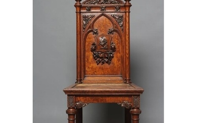 A VICTORIAN GOTHIC OAK HALL CHAIR, the arched back with turn...