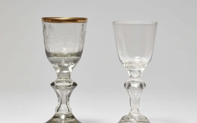A cut glass goblet with two coats-of-arms