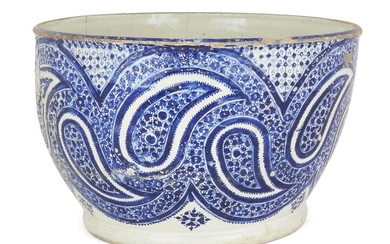 A large Qajar blue and white pottery bowl, Iran, late 19th/early 20th century, of deep rounded form, deocrated to body with design of swirling boteh motifs, 21cm. high x 32cm. diam.