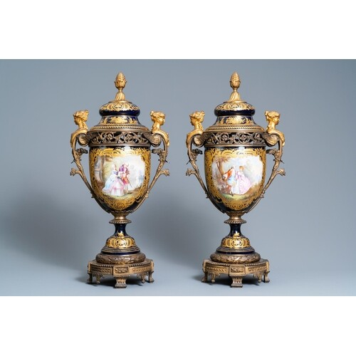 A pair of large French Sèvres-style vases with gilded bronze...