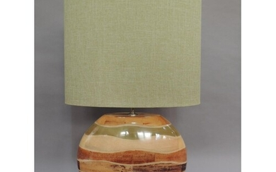 A wood effect strata table lamp of flattened moon shape on a...