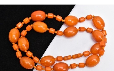 AN AMBER COLOURED BAKELITE BEAD NECKLACE, designed with thir...