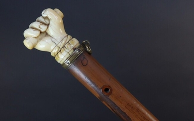 Cane with reed shaft. Pommel showing an ivory hand holding a stick. Mounted with a brass ring. Height 84,5 cm