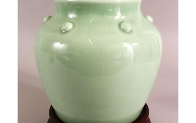 A CHINESE CELADON GLAZED VASE AND STAND, with a row of bosse...
