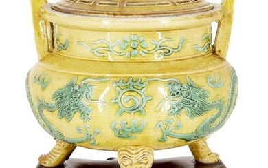 A Chinese porcelain yellow and green-enamelled 'dragon' censer and cover, 18th century, the exterior decorated with a pair of four-clawed dragons converging on a flaming pearl, the tripod legs moulded as feet protruding from the mouths of mythical...
