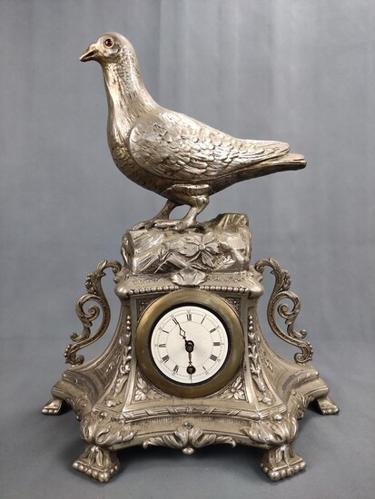 A table clock with a fully plastic dove, on a floral decorated base, clock face with Roman numbers