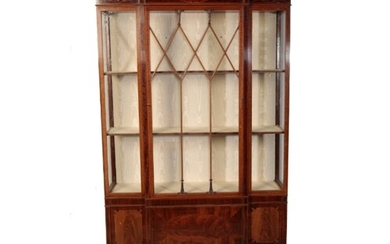 AN EDWARDIAN MAHOGANY BREAKFRONT DISPLAY CABINET in the mann...