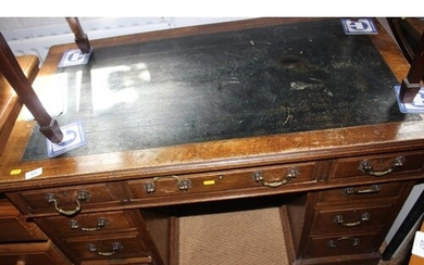 An Edwardian oak double pedestal desk with tooled lined top,...