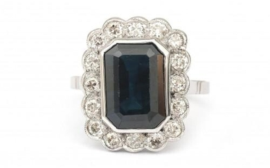A 14 karat white gold sapphire and diamond cluster ring. Featuring sixteen old European cut diamonds of ca. 0.64 ct. in total, ca. G-H, ca. VS surrounding an emerald cut sapphire of 5.70 ct. Gross weight: 7.9 g.