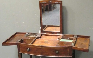 A George III mahogany bow front dressing table, the adjustable top revealing a mirror, the side