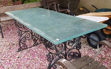 A painted cast iron garden table base, with later glass top,...