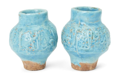 A pair of inscribed moulded Kashan turquoise glazed pottery vases, Iran, 13th century, of baluster form, 12.9cm. high (2) Provenance: Private collection London since 1968