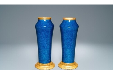A pair of monochome powder blue Sèvres vases with gilded bro...