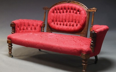 A Victorian walnut framed sofa, the carved back panel with oval upholstered backrest, flanked by curved sides, upholstered in crimson Damask pattern fabric, on front turned and fluted legs with castors